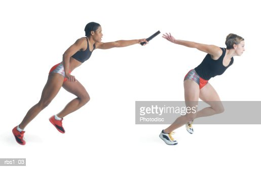 two female runners wearing black red and silver pass a baton as they run a race : Stock Photo