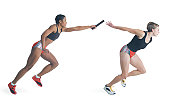 two female runners wearing black red and silver pass a baton as they run a race