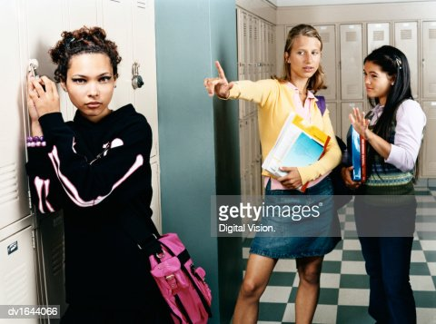 Two Female Secondary School Students Making Rejection Gestures Towards a Goth Girl : Stock Photo