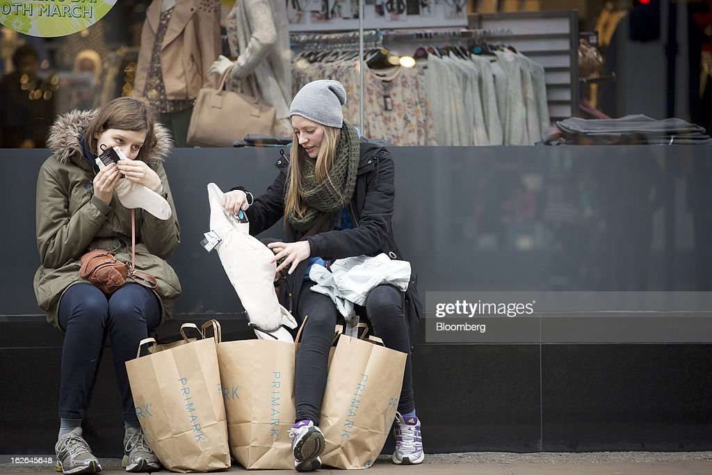 Two female shoppers sit and inspect their goods purchased from the Primark store on Oxford Steet, the store is operated by Associated British Foods Plc in central London, U.K., on Monday, Feb. 25, 2013. U.K. Chancellor of the Exchequer George Osborne won't bow to opposition calls to change economic plans after the decision by Moody's Investors Service to strip the U.K. of its Aaa status. Photographer: Jason Alden/Bloomberg via Getty Images