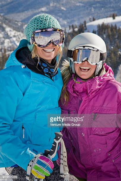 Two female skiers in helmets smiling and having fun on the ski slopes.