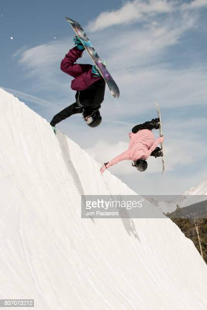 Two Female Snowboarders doing Simultaneous Handplants together