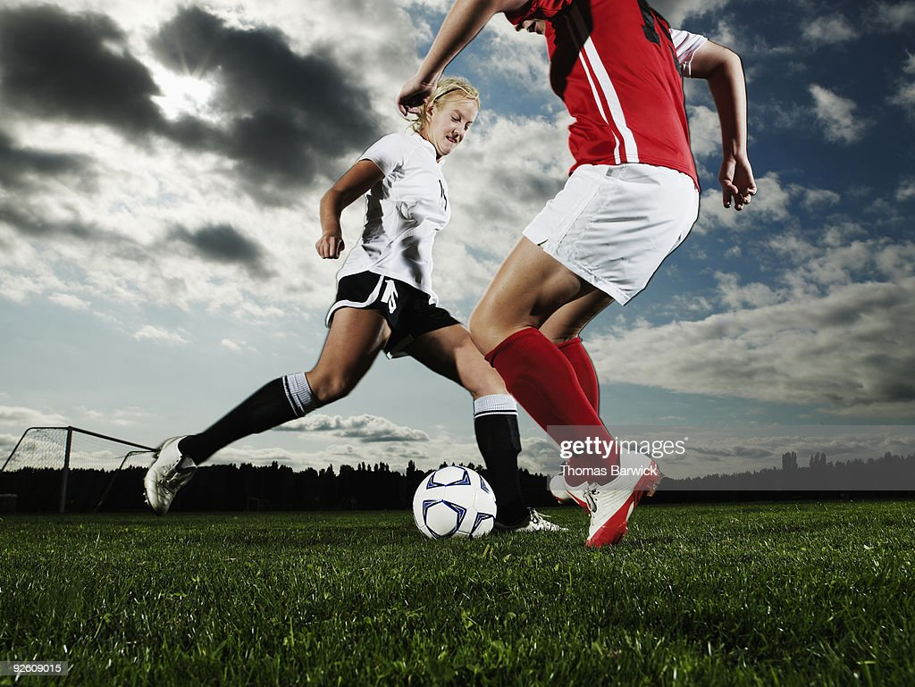 Two female soccer players converging on ball : Stock Photo