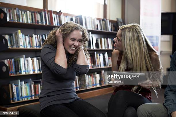 Two female students arguing in a library
