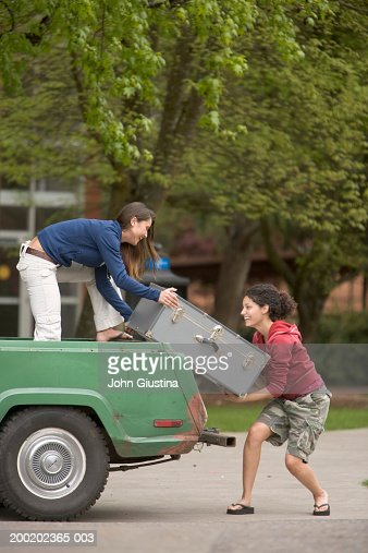 Two female students lifting trunk onto truck, side view : Photo