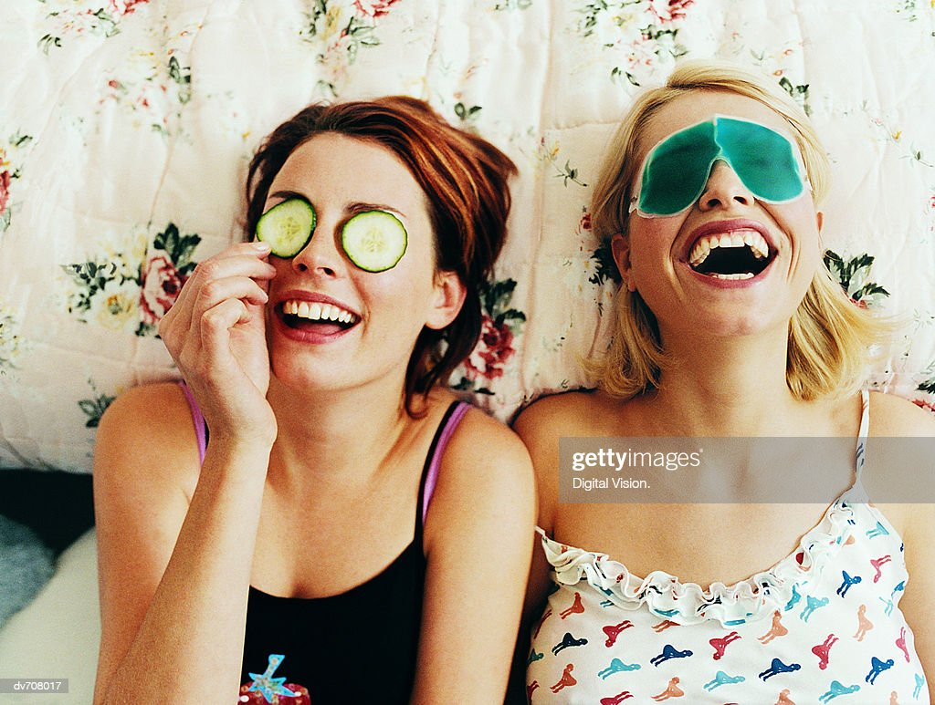 Two Female Teenagers Lying in Bed Wearing Eye Masks : Stock Photo