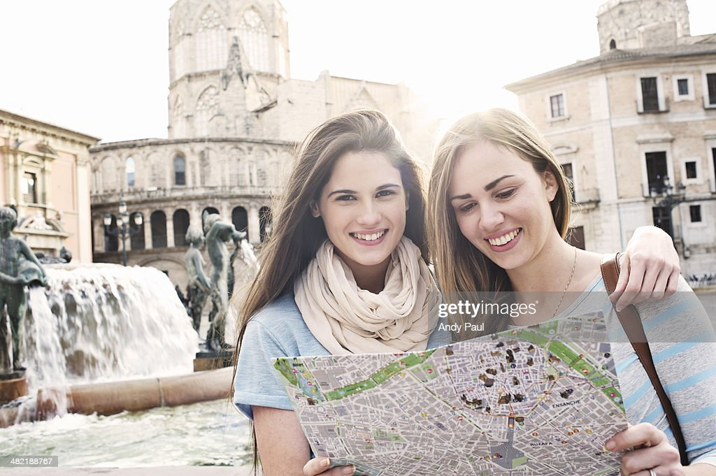 Two female tourists looking at map, Plaza de la Virgen, Valencia, Spain