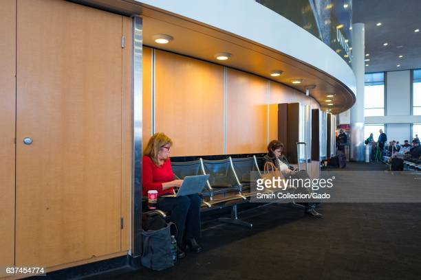 Two female travelers sit on benches and work on their laptops and smartphones while waiting for their flights in Terminal 2 at Los Angeles...