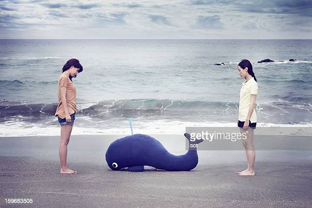 Two female with a whale in the beach