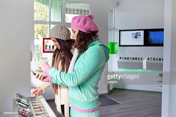 Two females at a mobile phone shop looking at cell phones