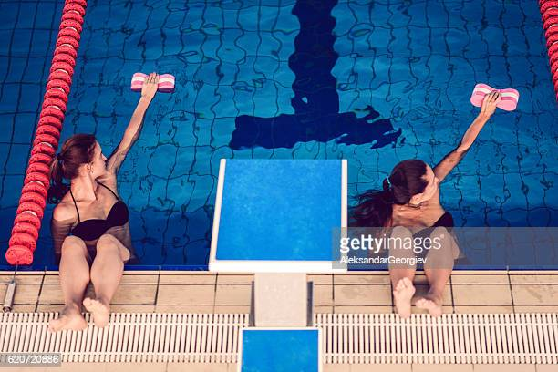 Two Females in Water Aerobics Class at Indoor Swimming Pool