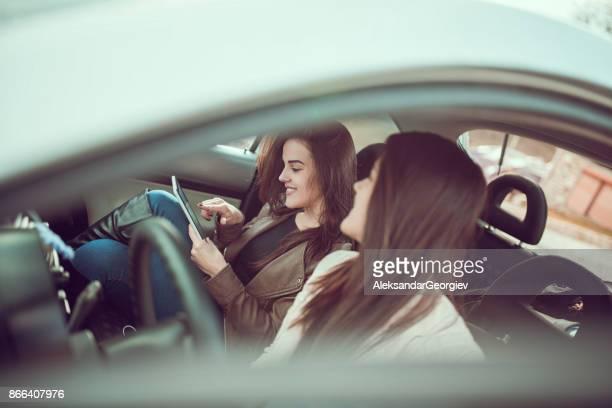 Two Females Making Travel Plans and Adjusting the Navigation on Digital Tablet