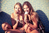 Two females sitting licking chocolate and vanilla ice creams