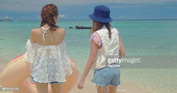 Two females walking on the beach.