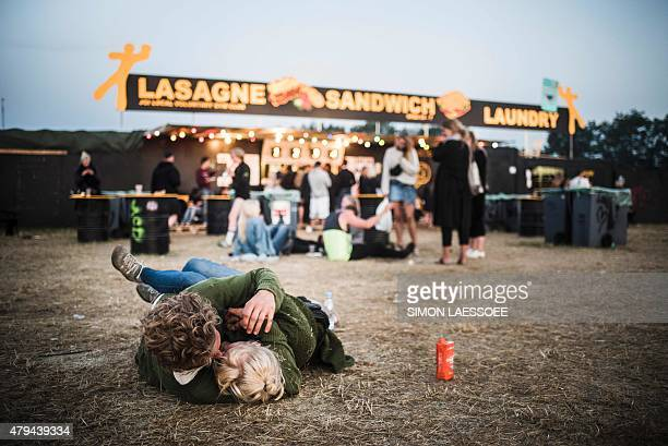 Two festival goers cuddle early in the morning during the annual Roskilde Festival in Roskilde Denmark on July 4 2015 This year's festival runs from...