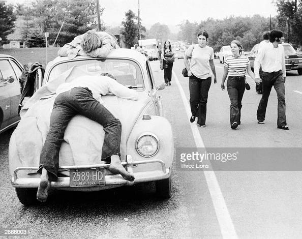 Two festival goers that found Woodstock too much lay passed out on the bonnet and roof of their Volkswagen Beetle