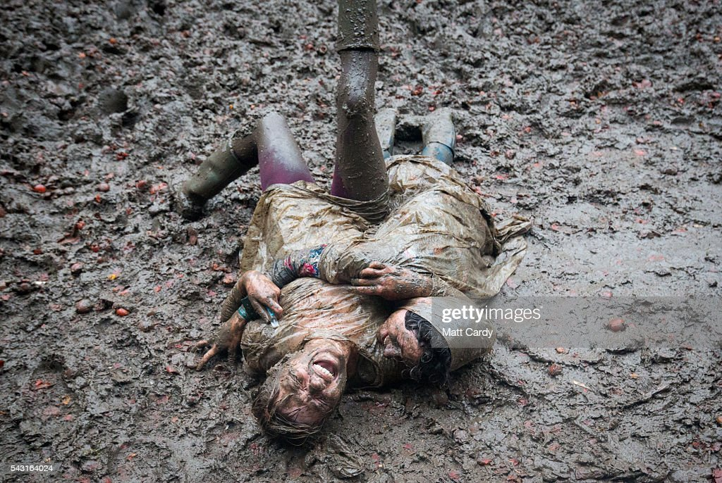 Two festival revellers roll in the mud after they took part in a tomato fight at the Glastonbury Festival 2016 at Worthy Farm, Pilton on June 25, 2016 near Glastonbury, England. The Festival, which Michael Eavis started in 1970 when several hundred hippies paid just £1, now attracts more than 175,000 people.
