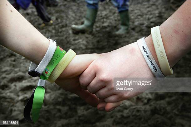 Two festivalgoers link hands in support of the Make Poverty History campaign on the second day of the Glastonbury Music Festival 2005 at Worthy Farm...