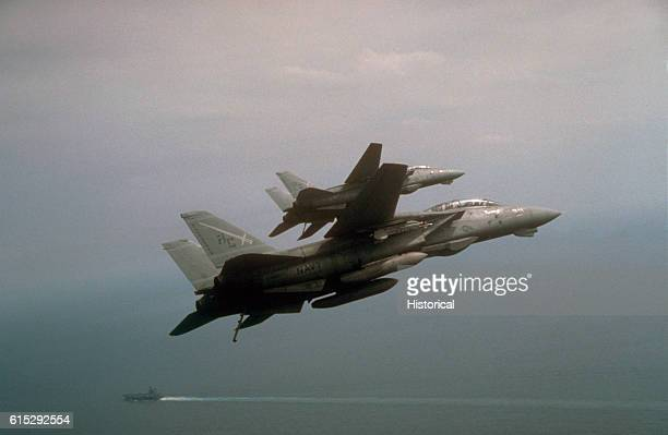 Two Fighter Squadron 32 F14A Tomcat aircraft bank toward the aircraft carrier USS John F Kennedy during Operation Desert Storm