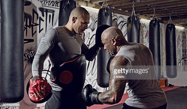 Two fighters sparring at an urban boxing gym