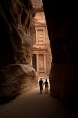 Two figures approach the lost city of Petra