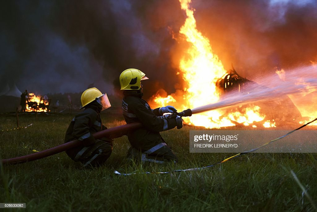 Two firefighters extinguish the eleven burning stacks of elephant tusks ivory and rhinoceros horns at Nairobi National Park on April 30, 2016 Kenyan President Uhuru Kenyatta set fire on April 30, 2016, to the world's biggest ivory bonfire, after demanding a total ban on trade in tusks and horns to end 'murderous' trafficking and prevent the extinction of elephants in the wild. / AFP / FREDRIK