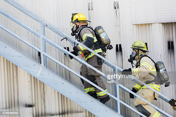 Two firefighters in protective gear climbing stairs