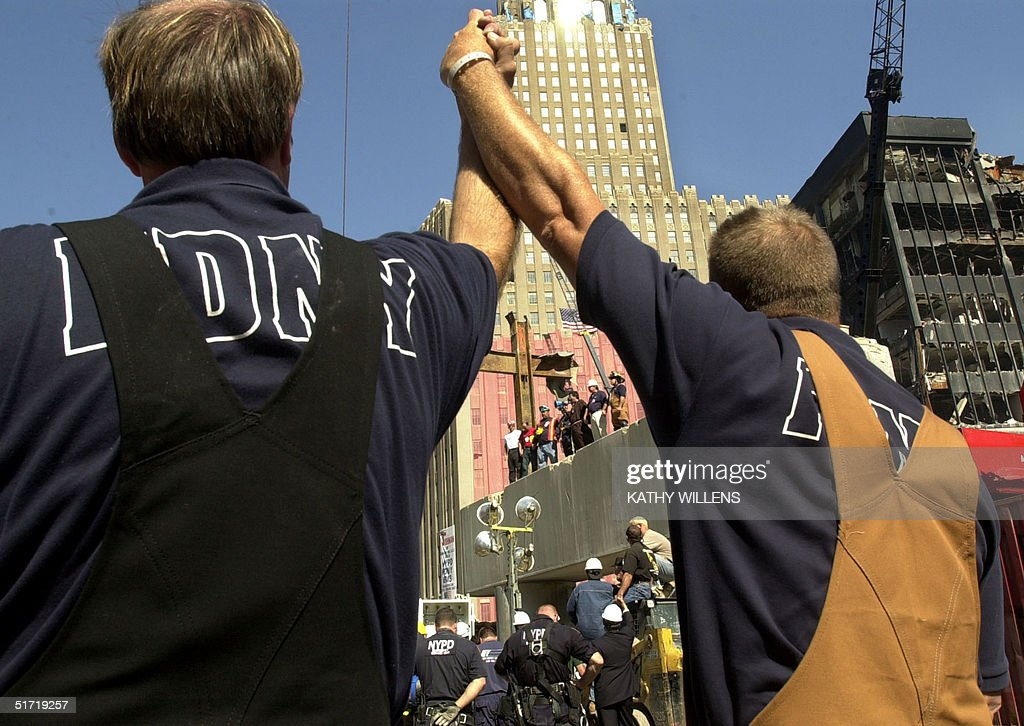Two firefighters join hands during a ceremony at which a cross of steel beams (C) is blessed 04 October 2001 at Ground Zero on the northwestern side of the World Trade tower attacks site. The cross was found by a laborer at the site two days after the twin towers' collapse and later moved to its present location. AFP Photo/Pool/Kathy Willens