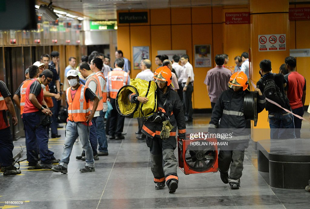 Two firefighters leave the scene with exhaust fan at Newton subway station in Singapore on February 13, 2013. An electrical fire at an underground train station disrupted metro services in Singapore but it was quickly put under control and no injuries were reported, authorities said. AFP PHOTO / ROSLAN RAHMAN