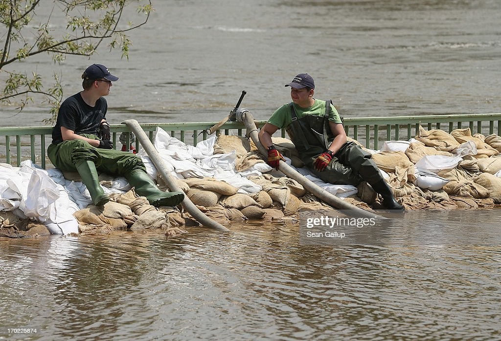 Two firefighters sit on sandbags in floodwaters as the swollen Elbe river churns behind on June 9, 2013 in Magdeburg, Germany. Magdeburg is enduring its highest floodwaters in its 1,200 year history and several city districts are underwater. Catastrophic flooding has hit portions of southern and eastern Germany that has left at least seven people dead and forced tens of thousands to flee their homes. Towns in northern Germany downstream from the Elbe are also bracing for floods in coming days.