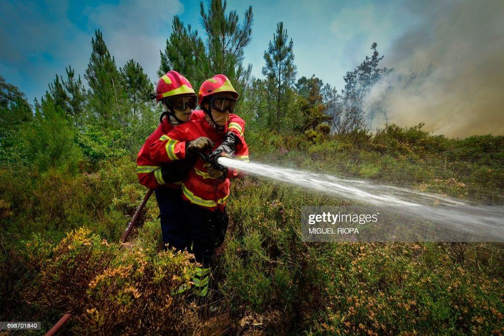 TOPSHOT - Two firefighters use a hose to combat a wildfire in Vale da Ponte, Pedrograo Grande, on June 20, 2017. The huge forest fire that erupted on June 17, 2017 in central Portugal killed at least 64 people and injured 135 more, with many trapped in their cars by the flames. RIOPA