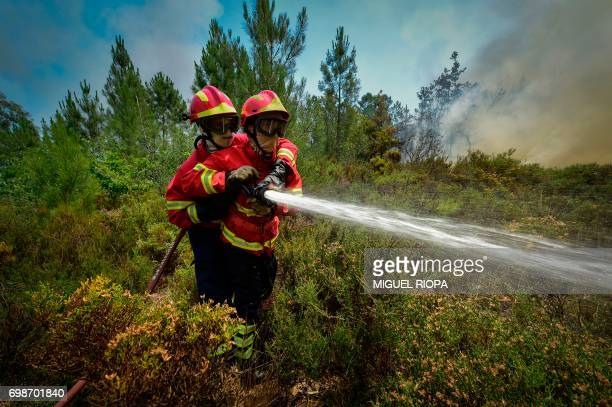 TOPSHOT Two firefighters use a hose to combat a wildfire in Vale da Ponte Pedrograo Grande on June 20 2017 The huge forest fire that erupted on June...