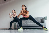 Two fit girls doing home workout performing lateral lunges at home.