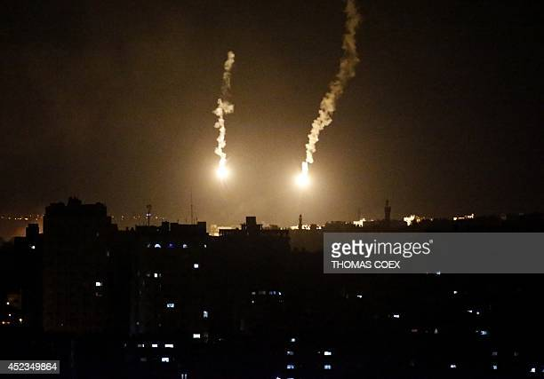 Two flares sent by Israeli army illuminate the eastern part of Gaza City on July 18 2014 Israel warned it could broaden a Gaza ground assault aimed...