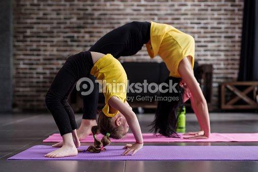 Dos chicas flexibles de diferente edad haciendo frente hacia arriba arco  pose de yoga trabajando   c42f9f158d73