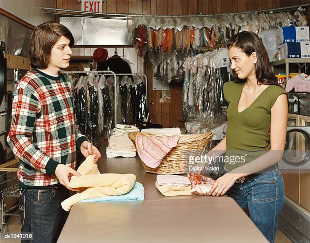 Two Flirtatious Twentysomethings Folding Their Laundry in a Launderette