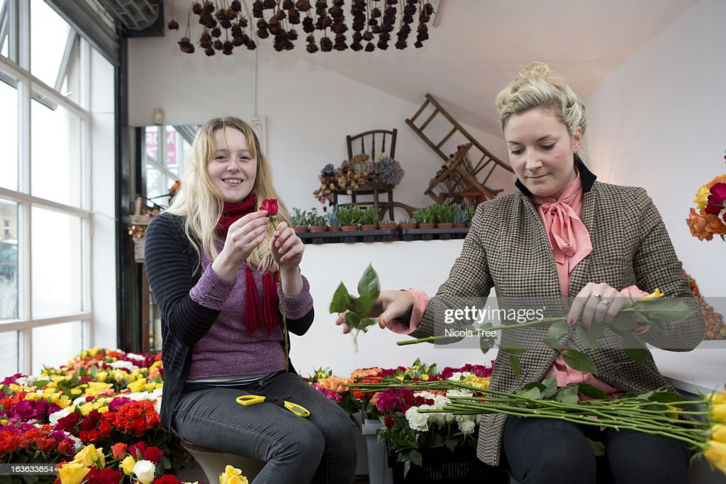 Two florists working together in their shop : Stock Photo