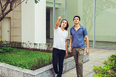 Portrait of two serious handsome young men walking, pointing and looking at something outdoors with building and flowerbed in background. Men friendship concept. Front view.
