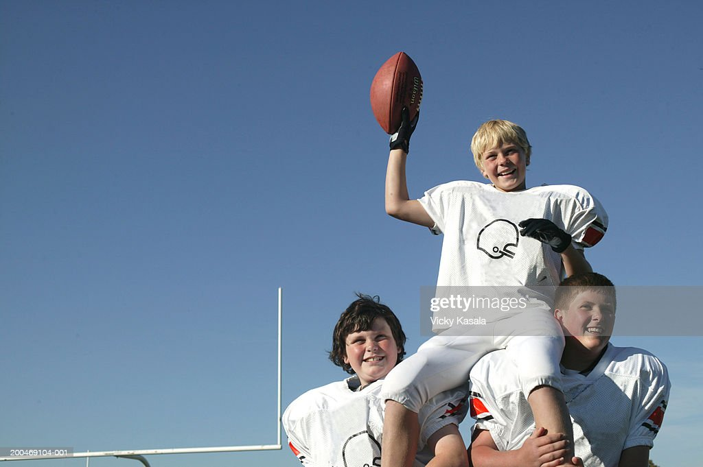 Two football players (10-12) carrying teammate on shoulders, smiling : Foto de stock