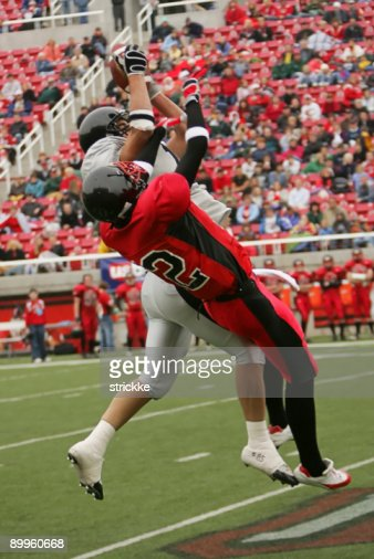 Two Football Players Jump Stretch for Airborne Ball : Stock Photo