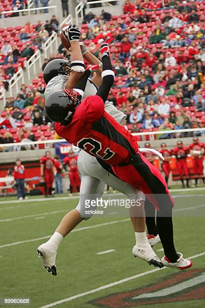 Two Football Players Jump Stretch for Airborne Ball