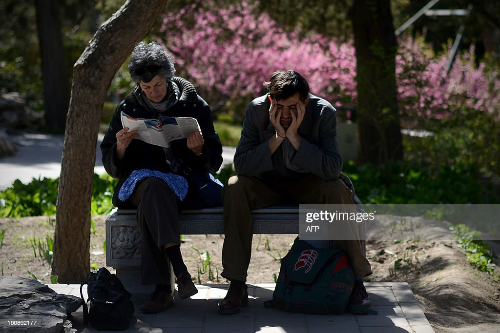 Two foreign tourists rest on a bench at a park in Beijing on April 18, 2013. The historic 700 year old park includes a 45 metre man-made hill which was built to provide a favourable Feng Shui environment for the nearby Forbidden City.