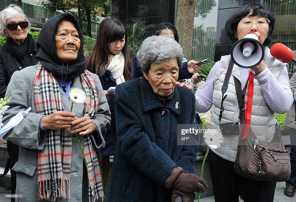 Two former 'comfort woman' Taiwanese Tao Cheng-Chen (C) and Estelita B. Dy (2nd L) of the Philippines lay flowers to mourn the death of former 'comfort women', during protests demanding Japan issue an official apology and justice, on International Human Rights Day in front of the building of the Interchange Association, Japan in Taipei on December 10, 2012. Former 'comfort women' from various countries have accused the Japanese government of inhumane crimes during World War II and are demanding an official apology and justice. AFP PHOTO / Mandy CHENG