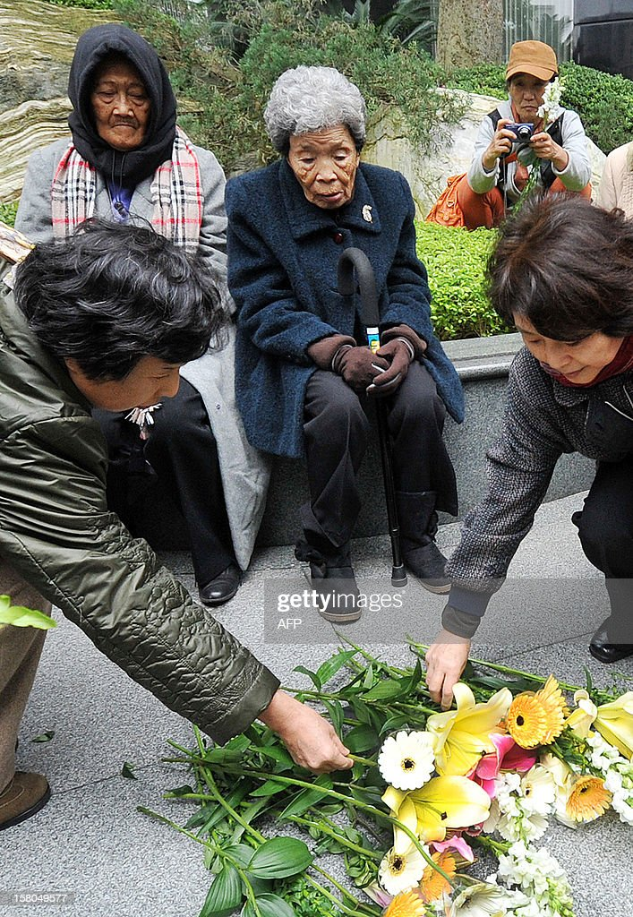 Two former 'comfort woman' Taiwanese Tao Cheng-Chen (C), Estelita B. Dy (sitting L) of the Philippines and supporters lay flowers to mourn the death of former 'comfort women', during protests demanding Japan issue an official apology and justice, on International Human Rights Day in front of the building of the Interchange Association, Japan in Taipei on December 10, 2012. Former 'comfort women' from various countries have accused the Japanese government of inhumane crimes during World War II and are demanding an official apology and justice. AFP PHOTO / Mandy CHENG