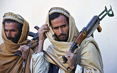 Two former Taliban fighters carry their weapons during a handover as they join a government peace and reconciliation process at a ceremony in...