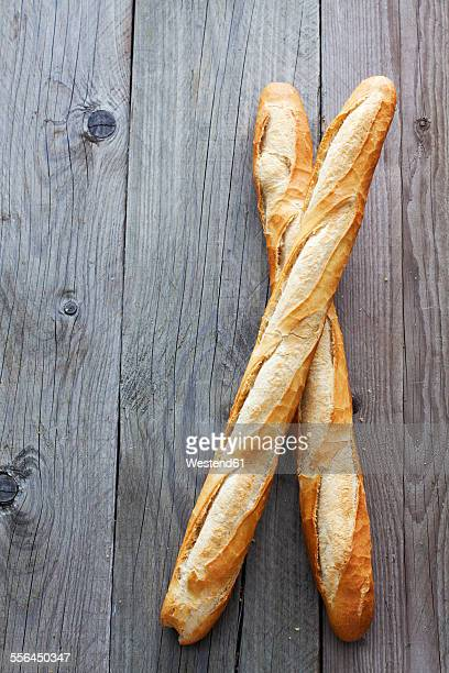 Two French baguettes on grey wood