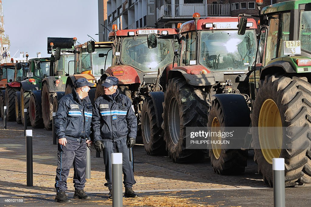 Two French police officers speak to each other while tractors block the road on January 2, 2014 in Dunkerque, northern France, during a demonstration by farmers called by the Gers farmers' union FDSEA to protest against the regional and ecological key measure of the Grenelle Environment, known as 'La Trame verte et bleue' (blue-green infrastructure).