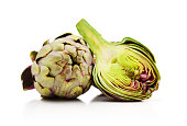 Two fresh artichokes with stem and a half showing the heart isolated on white background with clipping path