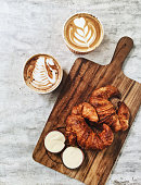 Two fresh crispy butter croissant on wooden plate and two hot aroma cappuccino. French breakfast, textured background