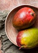 Two fresh mango in ceramic bowl